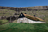 Woman in front of a hut with a grass roof in the village of Saksun on the island of Streymoy, Faroe Islands