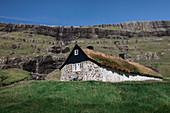 Frau vor Hütte mit Grasdach im Dorf Saksun auf der Insel Streymoy, Färöer Inseln\n