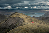 Woman hiking in the Faroe Islands landscape under dramatic clouds