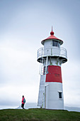 Woman at Skansin lighthouse in the capital, Torshavn, Faroe Islands