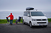 Man and woman with table and camping chairs in front of campervan by the sea on the Faroe Islands