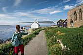 Woman photographs the church and ruin in the village of Kirkjubøur on Streymoy, Faroe Islands