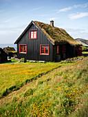 Schwarze Häuser mit roten Fenstern und Grasdach im Dorf Kirkjubøur auf Streymoy bei Sonne, Färöer Inseln\n