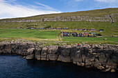 Coast at the village Kirkjubøur on Streymoy in the sun, Faroe Islands