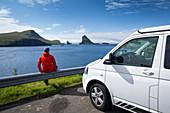 Man on campervan overlooking rock formations from Drangarnier on Vagar, Faroe Islands
