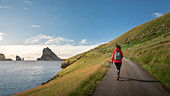 Woman hikes in sunshine in front of Drangarnier rock formations on Vagar, Bour, Faroe Islands