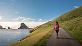 Frau wandert bei Sonnenschein vor Felsformationen von Drangarnier auf Vagar, Bour, Färöer Inseln\n