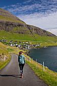 Frau wandert bei Sonnenschein beim Dorf Bour auf Vagar, Färöer Inseln\n