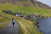 Woman walks in the sunshine by the village of Bour on Vagar, Faroe Islands