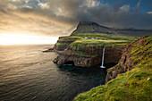 Sonnenuntergang am Wasserfall Múlafossur mit Dorf Gásadalur auf der Insel Vagar, Färöer Inseln\n