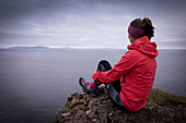 Woman with pink outdoor jacket on the cliff overlooking the sea, Faroe Islands