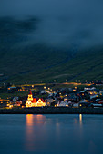 Illuminated church at night in the village of Sandavágur on the island of Vagar, Faroe Islands