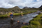 Hikers ford a river, Sisimiut, Greenland