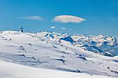 Steinplatte in winter with summit cross and Tyrolean Alpine panorama, Tyrol, Pillerseetal, Austria