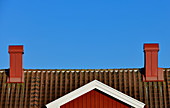 View of a red Swedish house against a blue sky with 2 chimneys, Grimsholmen, Halland, Sweden