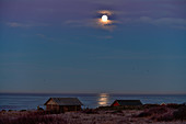 Fishing huts by the sea and the full moon conjures up a magical light, Grimsholmen, Halland, Sweden