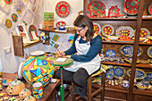 A craftswoman hand painting traditional ceramics, Erice, Sicily, Italy