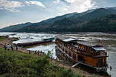 Passengers board the Mekong Sun river cruise ship on the banks of the Mekong River, Pak Tha District, Bokeo Province, Laos, Asia