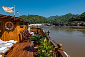 Frau entspannt sich auf Liegestuhl an Bord von Flusskreuzfahrtschiff Mekong Sun während einer Reise auf Fluss Mekong, nahe Pak Ou, Provinz Luang Prabang, Laos, Asien