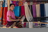 Woman weaves silk scarves on a loom in a local market, Pak Ou, Luang Prabang Province, Laos, Asia