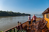 Couple on railing of river cruise ship Mekong Sun on river Mekong, Luang Prabang, Luang Prabang Province, Laos, Asia