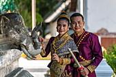 Happy wedding couple in gorgeous Laotian wedding attire during photo shoot at Wat Xieng Thong Temple, Luang Prabang, Luang Prabang Province, Laos, Asia