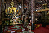 Young blonde woman admires the Buddha statue in the Buddhist temple Wat Xieng Thong (Temple of the Golden City), Luang Prabang, Luang Prabang Province, Laos, Asia