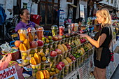 Young blonde woman at a market stall on Sisavangvong Road (the main street) which sells freshly squeezed fruit juice, Luang Prabang, Luang Prabang Province, Laos, Asia