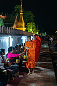 Barefoot monks collect early morning food and drink alms (sai bat), Luang Prabang, Luang Prabang Province, Laos, Asia