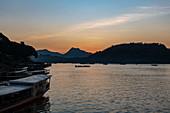 Tourist excursion boats lie on the banks of the Mekong River at sunset, Luang Prabang, Luang Prabang Province, Laos, Asia