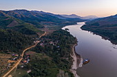 Aerial view of dirt road beside Mekong River with mountains in the distance at dusk, Ban Hoy Palam, Pak Tha District, Bokeo Province, Laos, Asia