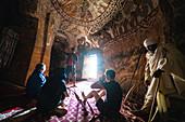 Tourists admiring fresco and paintings inside Abuna Yemata Guh church, Gheralta Mountains, Tigray Region, Ethiopia, Africa