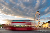A red London bus goes past in a blur across Westminster Bridge with the London Eye and Southbank in distance, London, England, United Kingdom, Europe