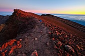 France, Reunion island, Cilaos, Salazie, hiker on the ridge of Piton des Neiges at sunset listed as World Heritage by UNESCO