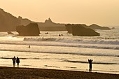 France, Pyrenees Atlantiques, Basque Country, Biarritz, surfer at the Grande Plage (town's largest beach) and the Rocher de la Vierge (Virgin rock) in the background