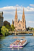 France, Bas Rhin, Strasbourg, old city listed as World Heritage by UNESCO, fly boat on Ill River with St Paul's Church in the background