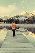 Woman on a jetty on Lake Staz, Engadin, Grisons, Switzerland, Europe