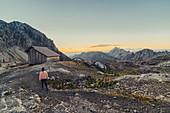 Woman enjoys sunrise in the mountains in Raetikon, Vorarlberg, Austria, Europe