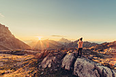 Woman with camera at sunrise in the mountains in Raetikon, Vorarlberg, Austria, Europe