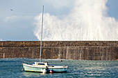 Boat behind the harbor wall at Goury on the Cotentin Peninsula, Normandy, France