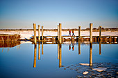 Walkers at the cutter harbor with mirror image, Dorum, Lower Saxony, Germany