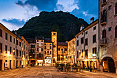 Evening view of Piazza Flaminio in the Serravalle district in Vittorio Veneto, in the background the Civic Tower and the Community Palace. Veneto region. Italy