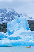 Kayaker paddling among icebergs, Torres del Paine National Park, Patagonia, Chile, South America