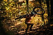 Mountain biker carries his bike through autumn forest, mountain biker, autumn, forest