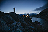 Man stands in front of mountain hut at night in the Swiss mountains, Switzerland, mountain range, mountaineering,