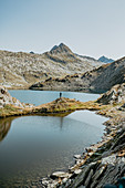 Mountaineer stands at a lake in the middle of the Swiss mountain range, Switzerland, mountains, lake, hiking,