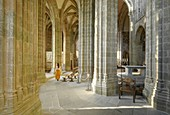 France, Manche, the Mont-Saint-Michel, young woman in church interior's and the Gothic choir