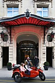 France, Paris, Royal Monceau hotel, woman riding in a retro side car in front of the hotel facade guarded by two valet