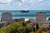 France, Seine Maritime, Le Havre, Downtown rebuilt by Auguste Perret listed as World Heritage by UNESCO, Perret buildings of Porte Océane (Ocean Gate) at the end of the Avenue Foch and a container ship in the background