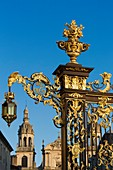 France, Meurthe et Moselle, Nancy, Stanislas square (former royal square) built by Stanislas Lescynski, king of Poland and last duke of Lorraine in the 18th century, listed as World Heritage by UNESCO, metal gate and railings covered with gold leaves by Jean Lamour, Notre Dame de l'Annonciation cathedral in the background